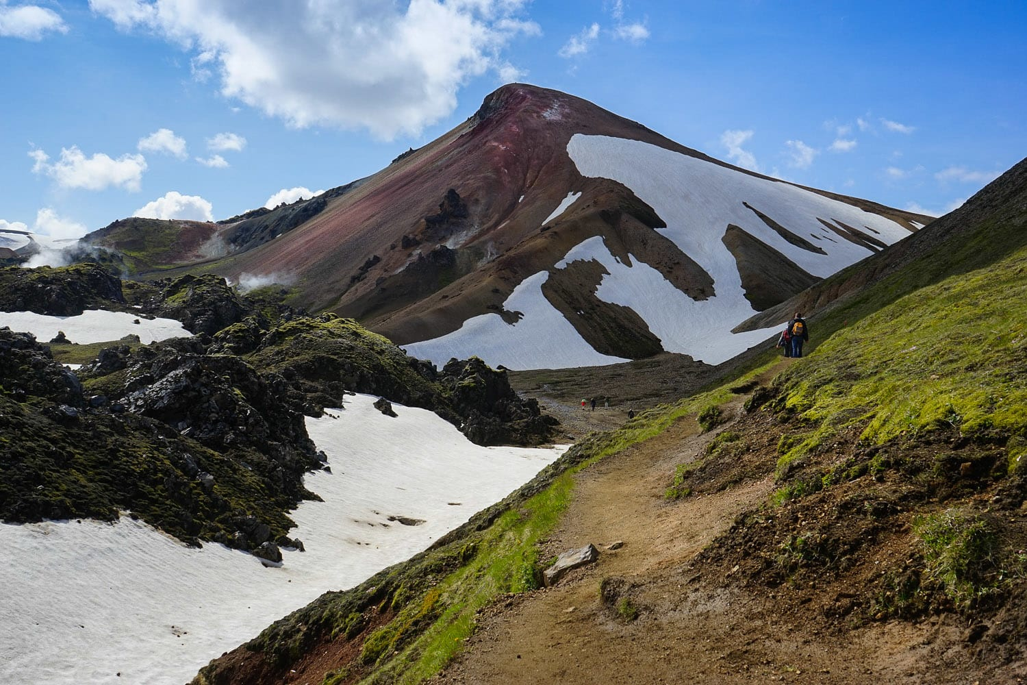 Hikers wandering between colorful mountains with snow, moss and steam patches