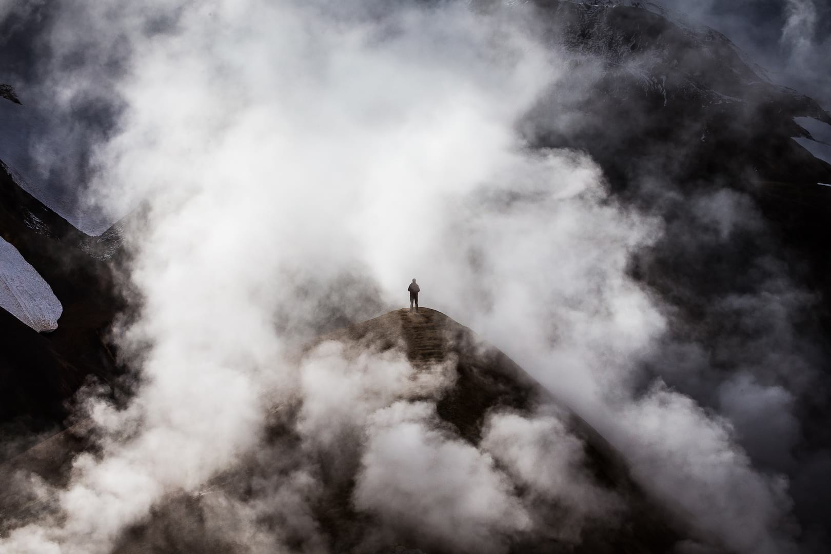 Lonely man standing in the steam on the Icelandic Highlands