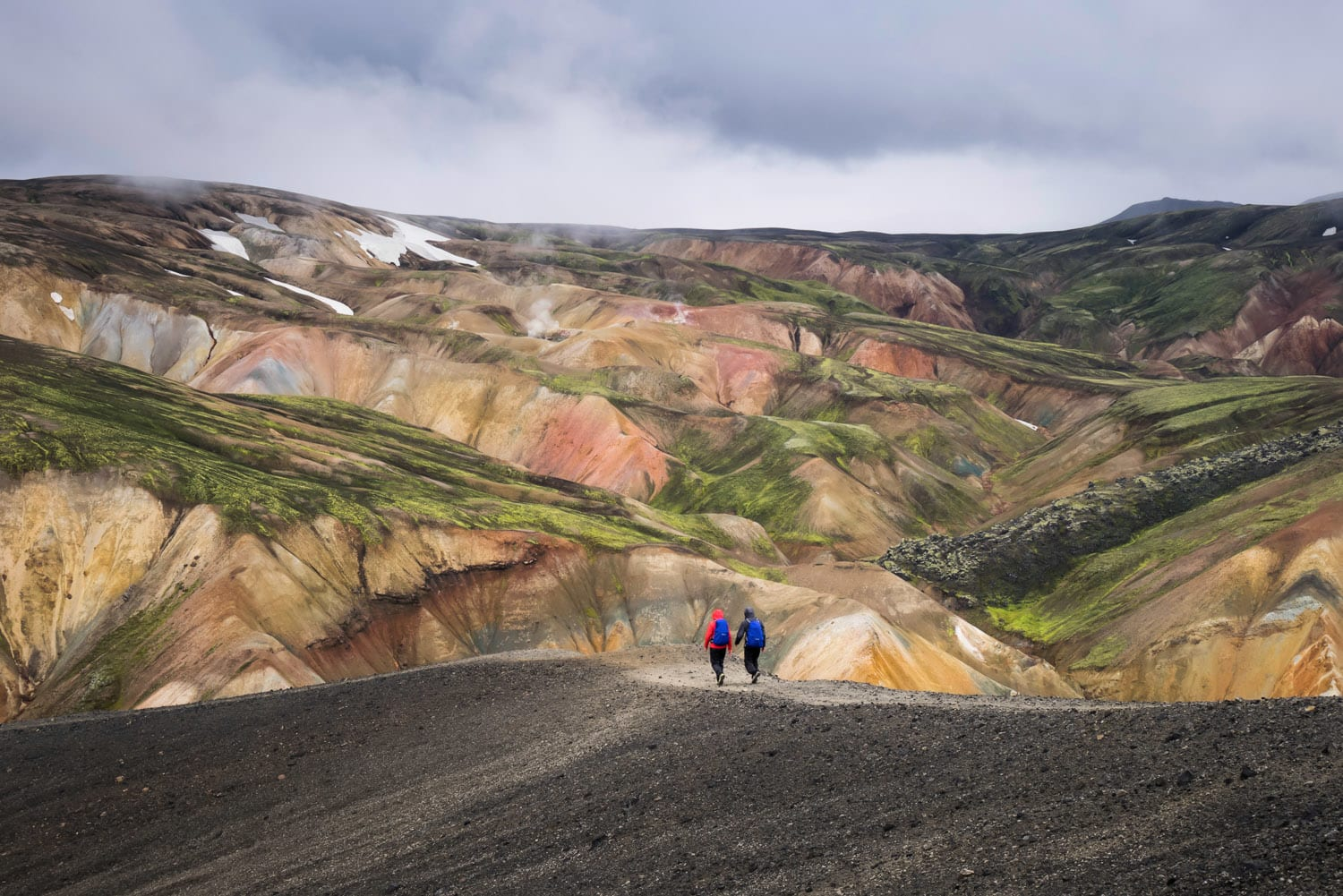 Hikers with backpacks walking on colorful mountains on Laugavegir trail