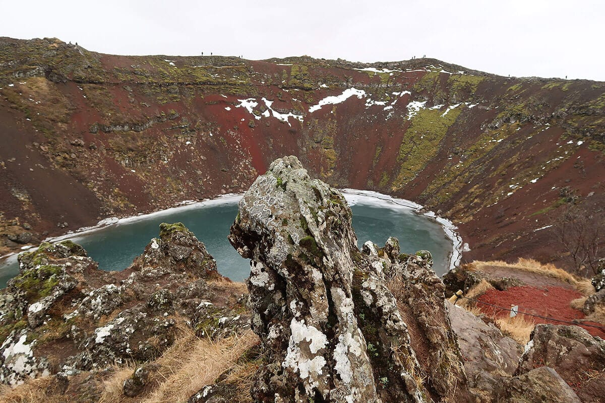 Kerid has a deep blue caldera surrounded by red rocks and beautiful lava formations